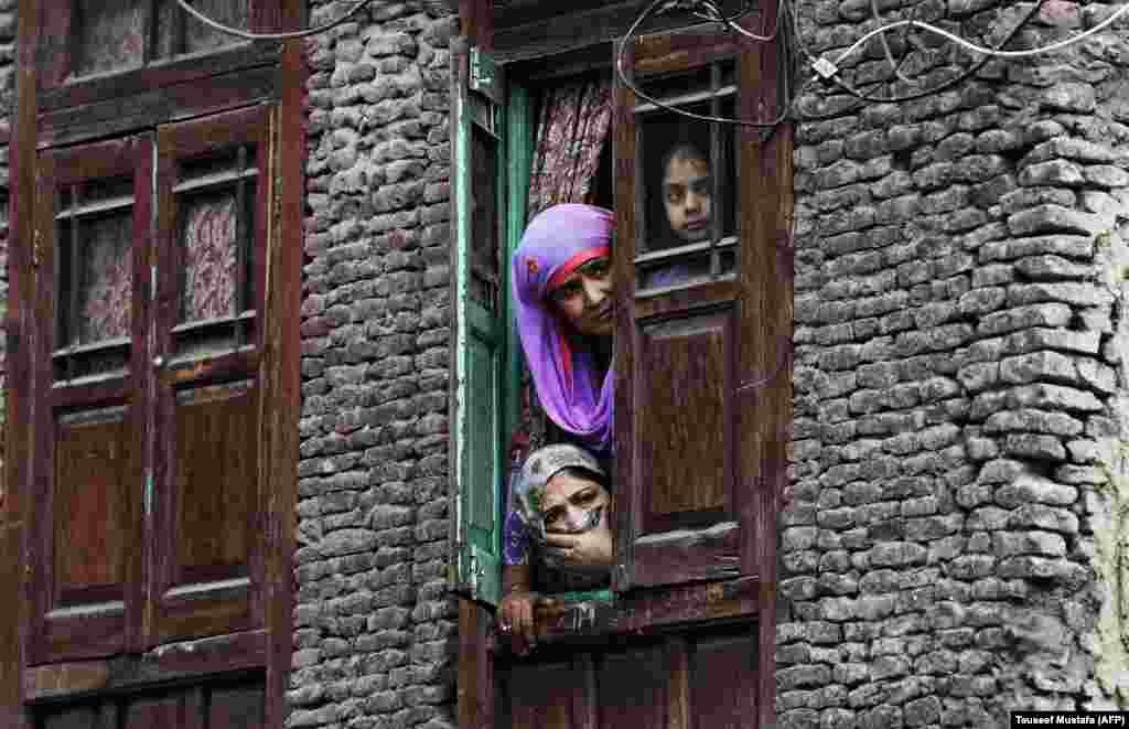 Local residents look out from a window near the site were a gunbattle took place between suspected militants and Indian government forces in downtown Srinagar, Kashmir, on October 17. (AFP/Tauseef Mustafa)