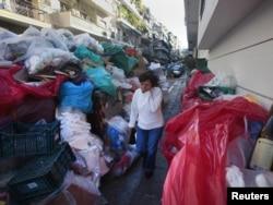 Žena prolazi sa zatvorenim nosem pored naslaga smeća koje sa ulica atine nije sklanjano skoro dve nedelje, 19. oktobar 2011.