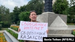"Kazakh civic activist Anna Shukeeva holds a placard reading ""Internet freedom -- freedom in Kazakhstan"" in Nur-Sultan on July 26."