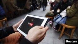 Youtube сайтын планшеттен қарап отырған адам. (Көрнекі сурет)