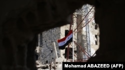 SYRIA -- The Syrian national flag rises in the midst of damaged buildings in Daraa-al-Balad, an opposition-held part of the southern city of Daraa, on July 12, 2018.