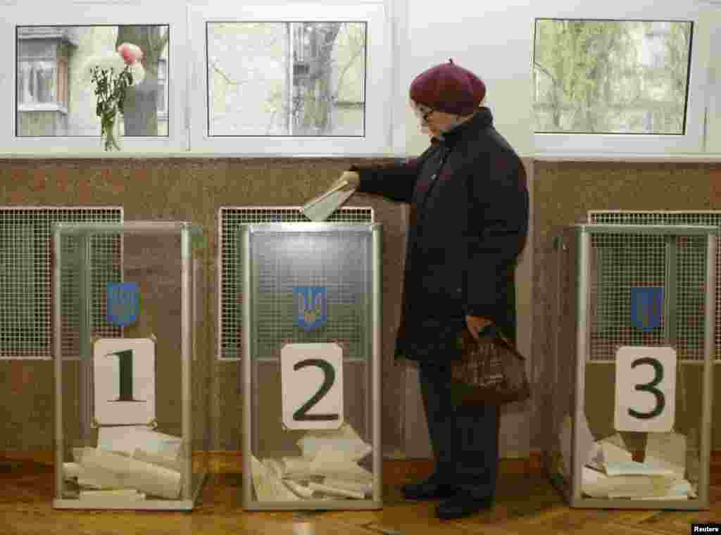 A woman casts her vote at a polling station in Kyiv.
