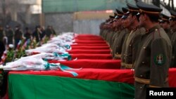 Afghan honor guards stand next to coffins as they pay tribute to soldiers who were killed in an Taliban attack in Kunar province.