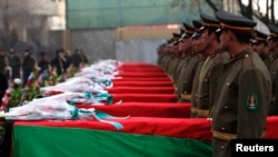 Afghan honor guards stand next to coffins as they pay tribute to soldiers who were killed in an Taliban attack in Ghaziabad district of Konar Province, during a tribute ceremony in Kabul on February 24.