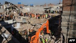 Rescue workers continue their search for victims in the debris of a collapsed building in Lahore.