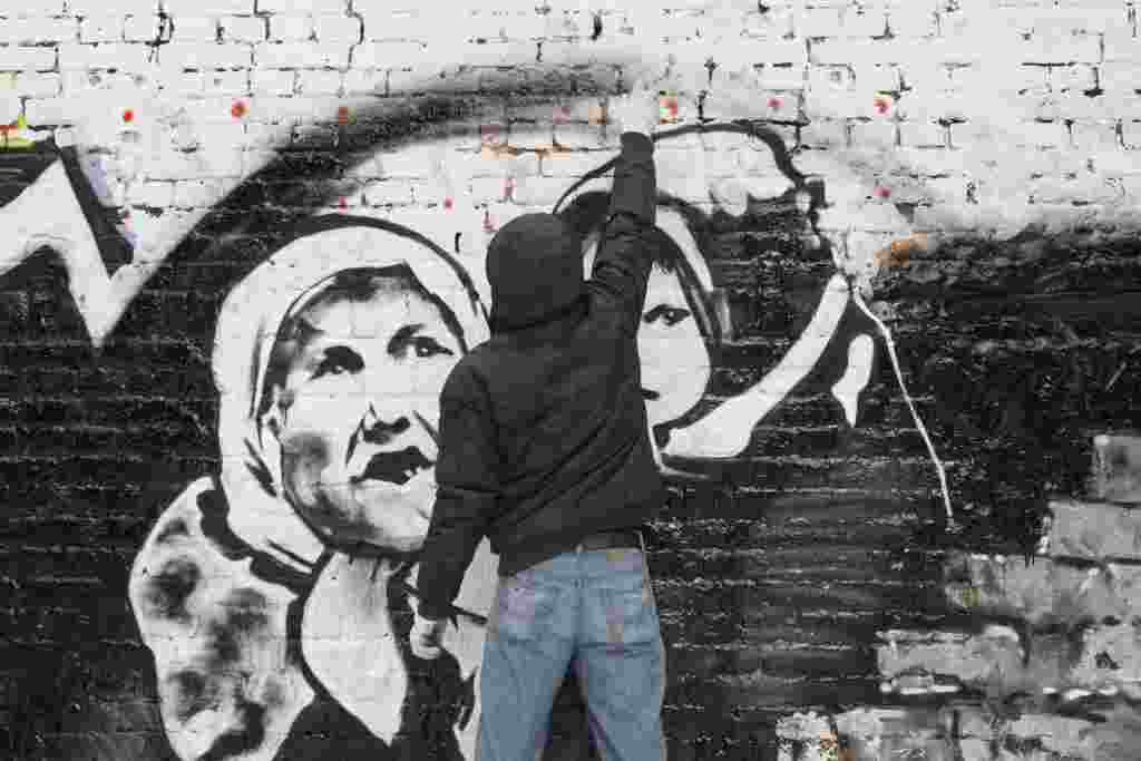 Street artist P183 paints a mural ahead of last year's Russian presidential election on a wall in central Moscow.
