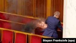 UKRAINE -- A lawmaker tries to get out a burning smoke bomb from Parliament's session hall, in Kyiv, October 6, 2017