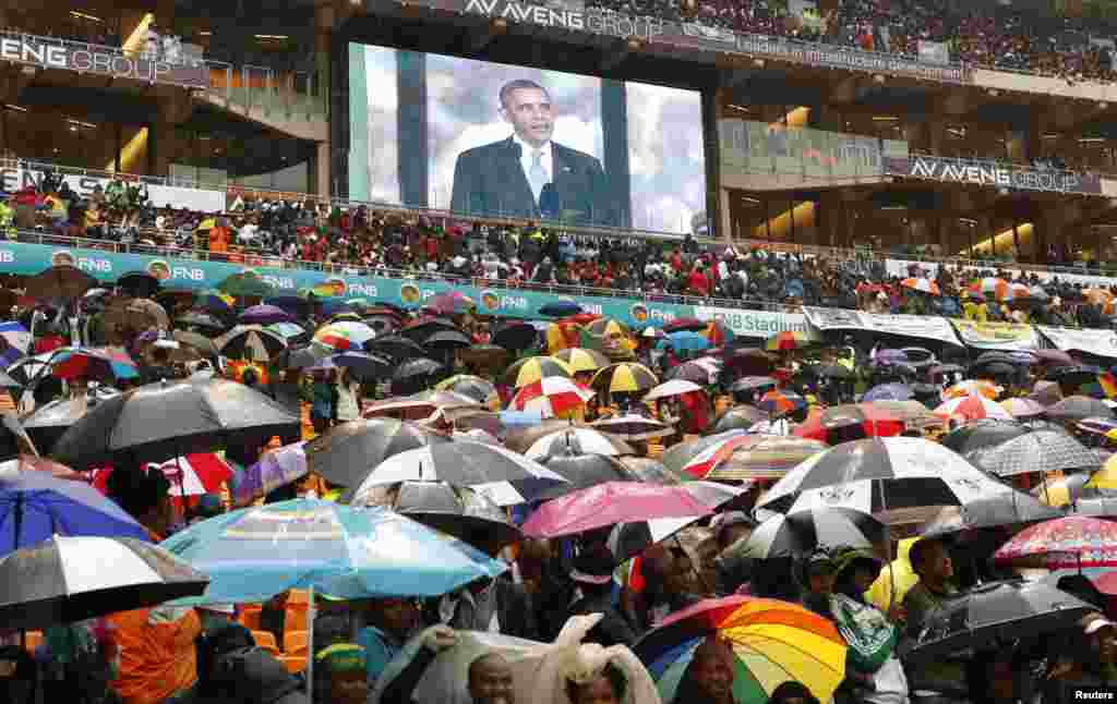 "South Africans listen in the rain to U.S. President Barack Obama, who praised Mandela as a ""giant of history."""