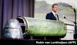 Председатель международной Совместной следственной группы Фред Вестербеке во время выступления. А на столе части ракеты российской установки «Бук», которая уничтожила «Боинг» на Донбассе летом 2014 года. Нидерланды, 24 мая 2018 года