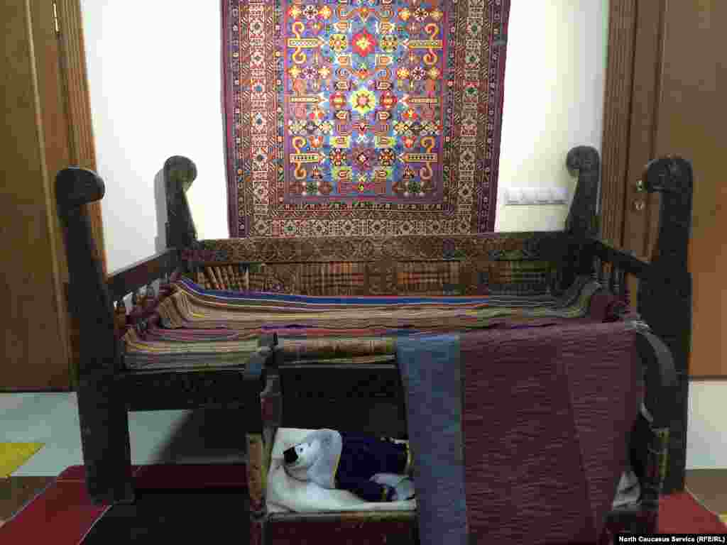 На переднем плане - деревянная колыбель. Сзади - тахта (своего рода диван) и ковер ручной работы