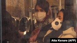 شهروندان در تهران در حالی که صورت خود را با ماسک و دستان خود را دستکشهای پلاستیکی پوشاندهاند سوار بر اتوبوس؛ ایران یکی از کانونهای اصلی شیوع ویروس کرونای جدید در خارج از کشور چین است.