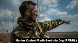 Український військовий показує в напрямку позицій підтримуваних Росією бойовиків