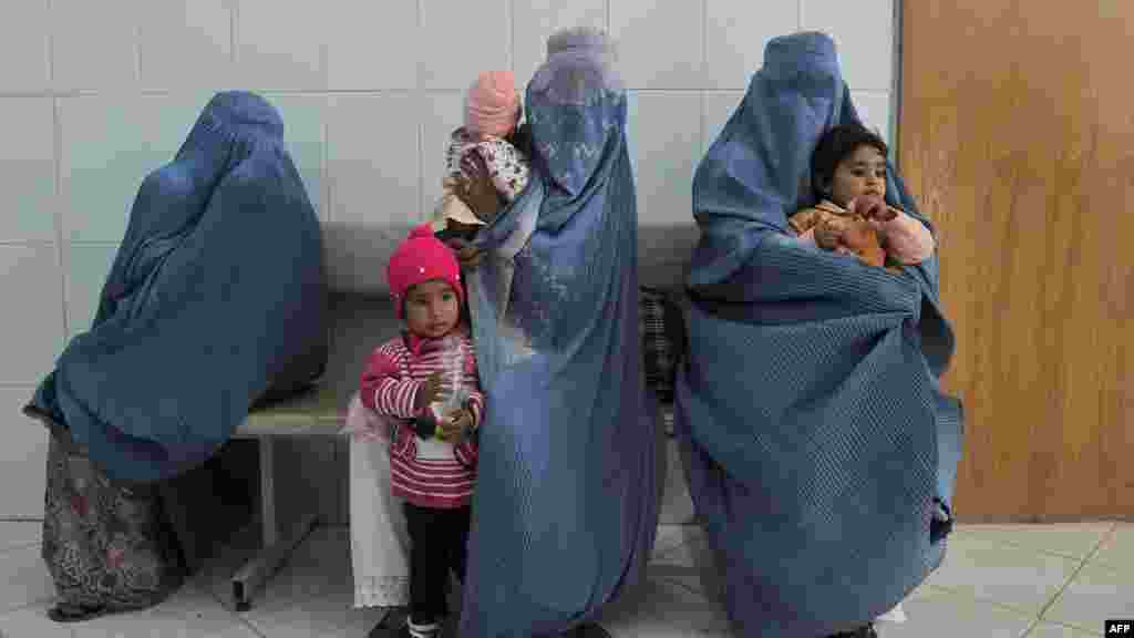 Women wait with their children for polio vaccinations on the second day of a vaccination campaign in western Afghanistan in October. Attackers have targeted health workers there, too, including a deadly shooting in eastern Afghanistan on December 1. (AFP/Aref Karimi)