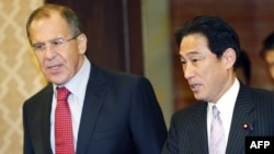 Japanese Foreign Minister Fumio Kishida (right) talks with his Russian counterpart, Sergei Lavrov, prior to their meeting in Tokyo.