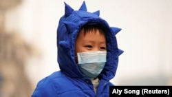 پسر بچهای در شانگهای در حالی که در اوج شیوع ویروس کرونا ماسک بر صورت زده است. در ۱۵ فروردین نیمی از جمعیت جهان در قرنطینه قرار گرفته و یک میلیون نفر به ویروس کرونا مبتلا شدهاند.