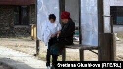 Женщина с ребенком на автобусной остановке на окраине Астаны.