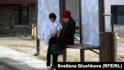 Аялдамада отырған әжесі мен немересі. Астана, 16 қазан 2011 жыл. (Көрнекі сурет)
