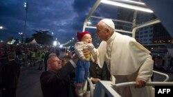 Папа римский Франциск благословляет малыша, которого держит на руках верующий отец. Рио-де-Жанейро, 26 июля 2013 года.