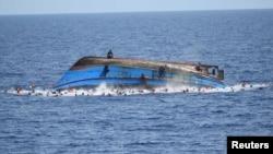 Спасатели пытаются спасти мигрантов с перевернутой лодки близ Италии. 25 мая 2016 года.