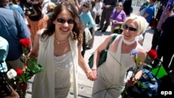 A soon-to-be-married couple works their way through the crowd outside City Hall in San Francisco in June 2008.