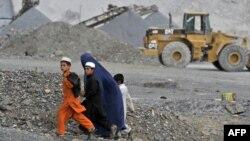 Афганская женщина с детьми идет вдоль карьера. 5 октября 2011 года.