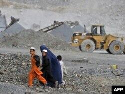 Балаларын ерткен әйел карьер жанынан өтіп барады. Ауғанстан, 5 қазан 2011 жыл. (Көрнекі сурет)