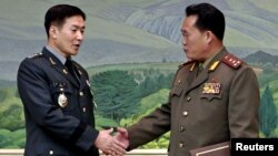 Korea -- South Korean colonel Moon Sang-kyun (L) and his North Korean counterpart colonel Ri Shin-kwon pose before their talks at the Peace House on southern part of the truce village of Panmunjom in the demilitarized zone in Paju, 30Sep2010