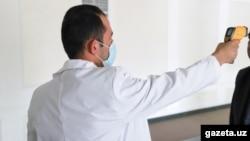 Врач проводит контроль термодатчиком для определения температуры у гражданина Узбекистана. Фото с сайта Gazeta.uz.