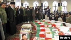 Supreme Leader Ayatollah Ali Khamenei (second from left) and Revolutionary Guards commander Mohammad Ali Jafari (left) stand next to the coffins of 17 members of the Revolutionary Guards who were killed in a blast at a military base last week.