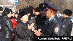 Полиция қызметкері азаматтарға ескерту жасап тұр. Алматы. 18 қараша 2013 жыл.