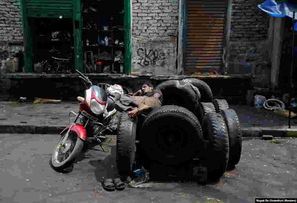 A worker rests on used tires in front of an automobile repair shop in Kolkata, India.
