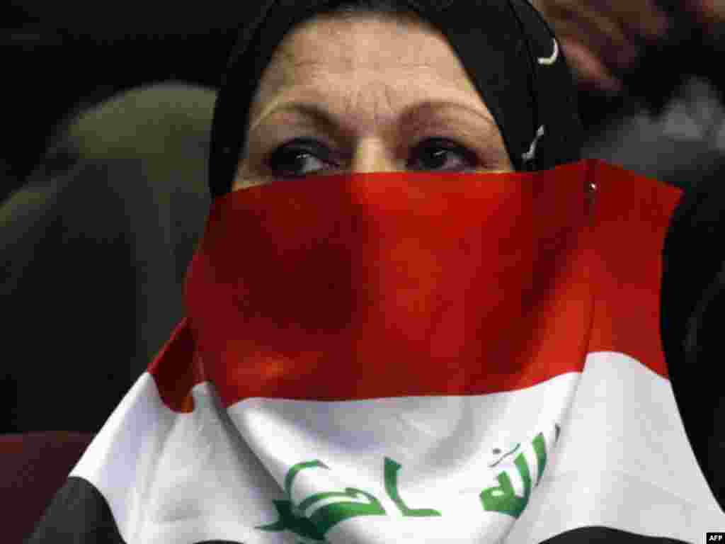 A woman covers her face with the national flag during a ceremony marking Teacher's Day in Baghdad. - Photo by Ahmad al-Rubaye for AFP