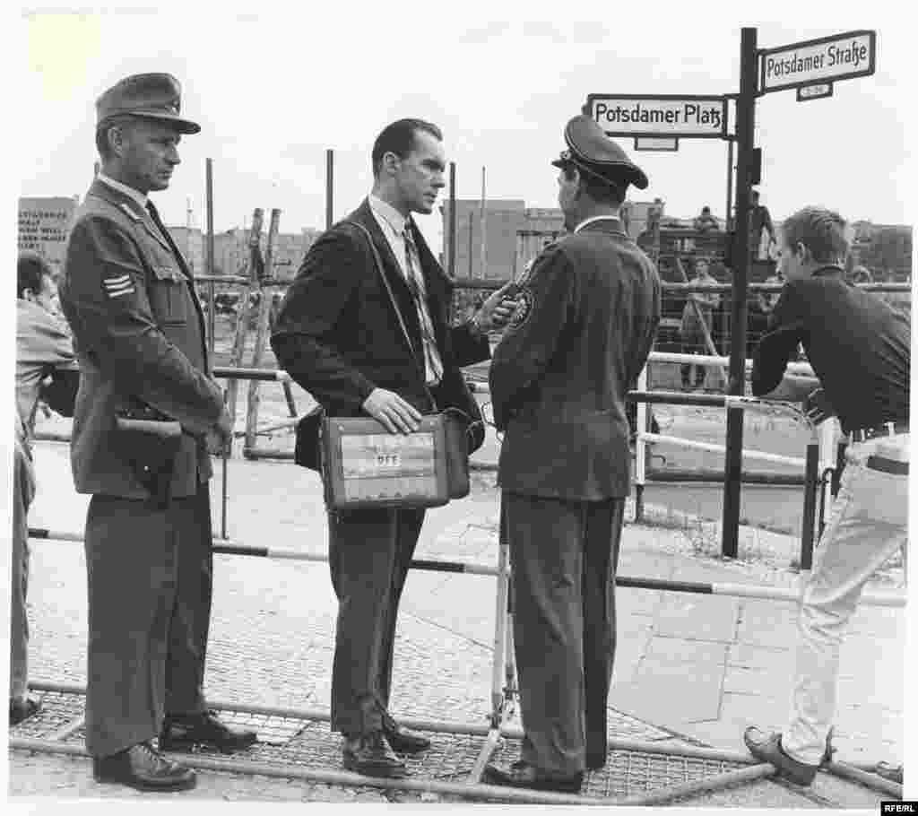 William Marsh, Berlin bureau chief of Radio Free Europe, interviews a police official at Potsdamer Platz. - In the background, East German workers are erecting the permanent wall, which bisected Potsdamer Platz and rendered the square a desolate wasteland.
