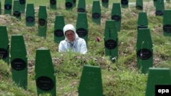 A Muslim woman visits the grave of her brother next to the graves of other victims of the killings by Serb forces in Srebrenica in 1995.