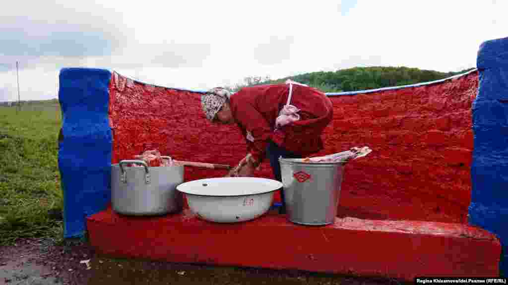 Женщины промывают крупу и мясо в родниковой воде