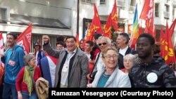 Ортада жұдырығын көтеріп тұрған қазақстандық құқық қорғаушы әрі журналист Рамазан Есіргепов. Париждегі саяси шаралардың бірі, 2017 жылдың күзі.