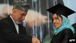 Afghan President Hamid Karzai shakes hands with a female student during a university graduation ceremony in Kabul.