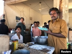 Chef (holding a plastic plate) at the Bhittai restaurant, Khorwah, in Sindh's Badin district. The village is lit by solar power.