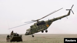 An MI-17 helicopter flies by an armored personnel carrier in Kazakhstan (file photo).
