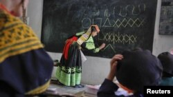 A teacher writes letters from the Kalasha alphabet on a blackboard during a lesson at the Kalasha Dur school and community center in a village in the Bumboret Kalash valley.