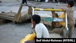 اطفال في الكوت يعملون في نقل البضائع