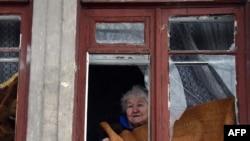 Жінка виглядає у вікно після обстрілу в Куйбишевському районі Донецька, січень 2015 року