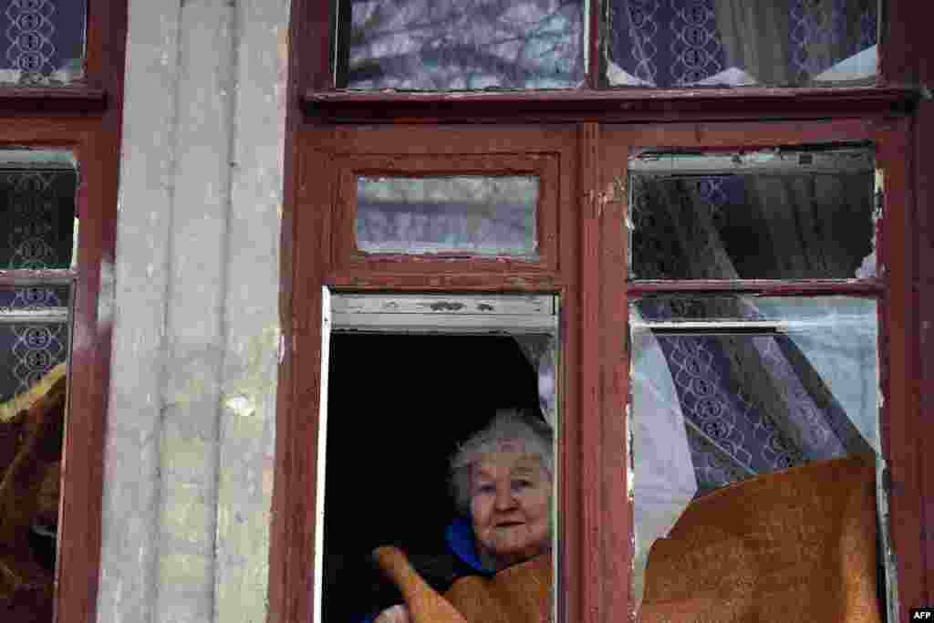 An elderly woman looks on after a shell hit a residential area in Donetsk's Kyibishevsky district.