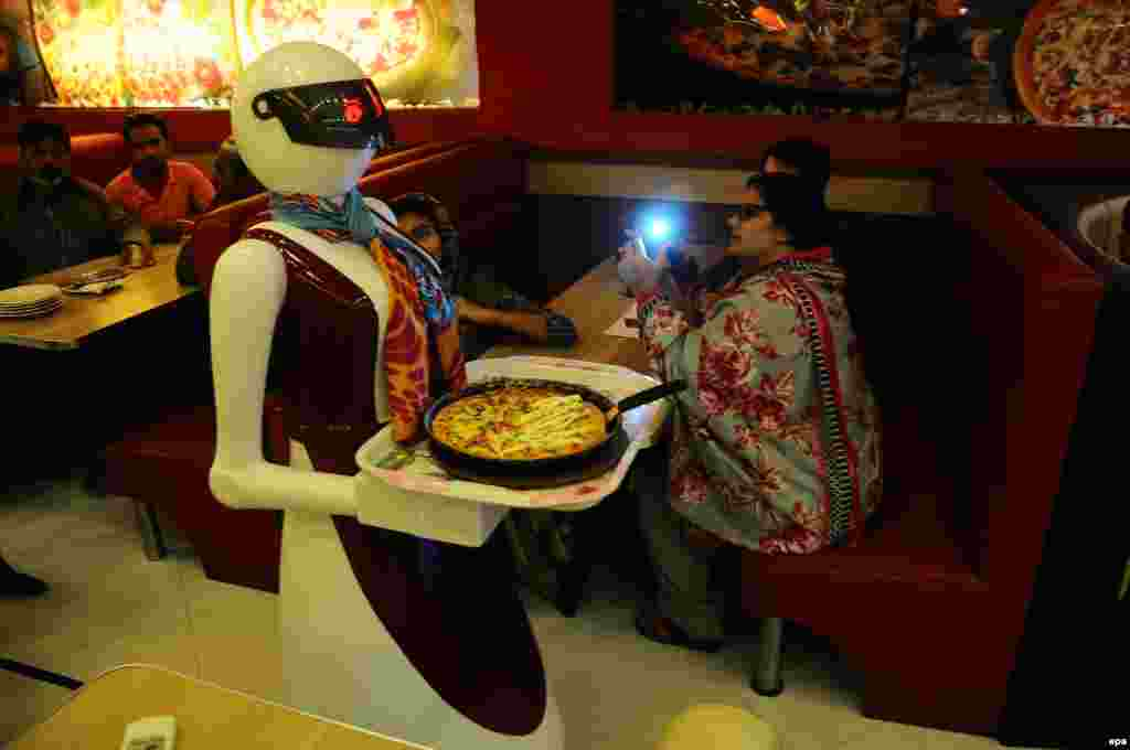 A robot waiter serves pizza to customers at the Pizza.com restaurant in Multan, Pakistan. Syed Usama Aziz, an electrical engineering student, created the robot waiter for his father's business. According to reports, it took Aziz about eight months and $3,800 to build the robot. (epa/Faisal Kareem)