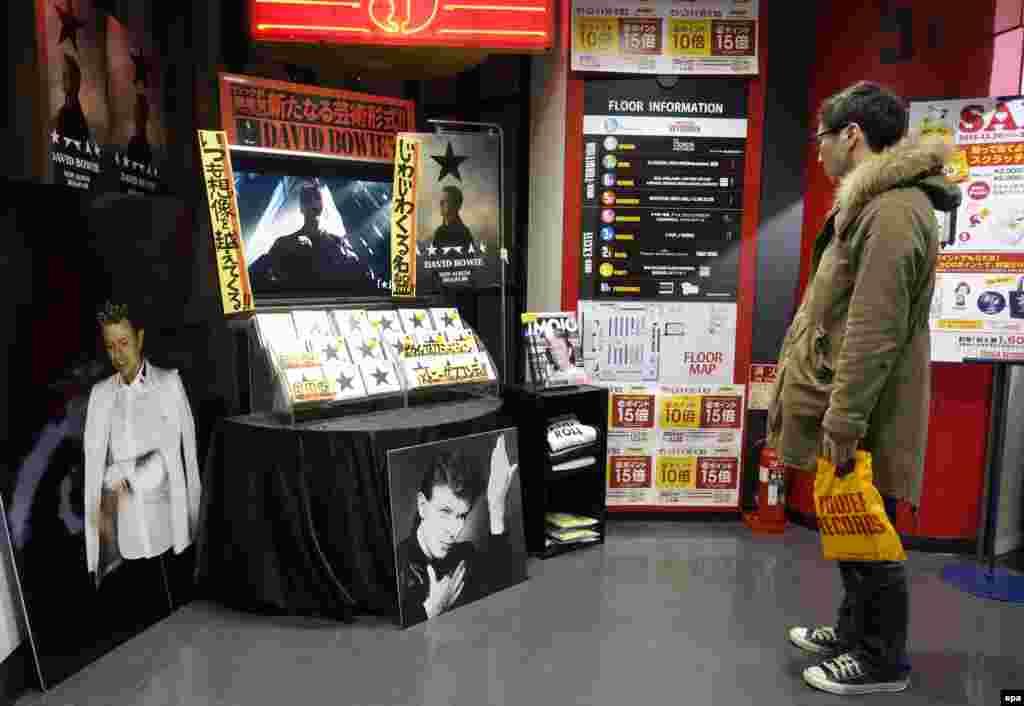 """Снимок сделан 11 января 2016 года в день смерти Дэвида Боуи. Покупатель в музыкальном магазине в Токио смотрит на выставленный на витрине последний альбом Боуи """"Черная звезда"""""""