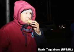Участник акции протеста ест пирожок, которые на площади раздавала сочувствующая забастовщикам жительница города. Актау, 20 декабря 2011 года.