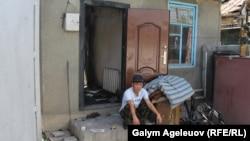 Мужчина сидит на крыльце горевшего дома на улице Жамбыла Тобаякова. Алматы, 7 августа 2015 года.