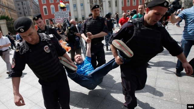 "Police officers detain a protester in Moscow last year. According to Freedom House, 2015 saw Russia and other authoritarian regimes ""crack down harder on dissent."""