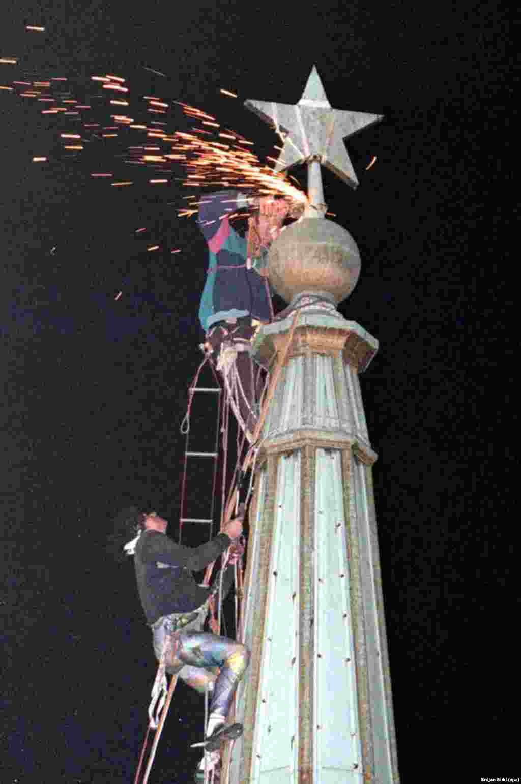 Climbers cut off the communist star from the tower of Belgrade's town hall in 1997 after months of street protests in the Serbian capital.