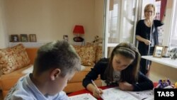 Boy and girl do grammar exercises during a private lesson